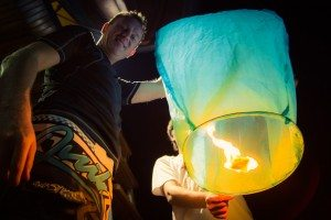 Lighting the lanterns. Photo credit: Another Traveler